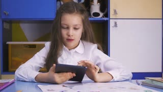 Cute little Girl Studying at the Library Doing Homework with tablet PC. Elementary school. Child reading