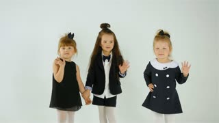 Cute Little Girls Wave At The Camera, Isolated On White Studio Shot