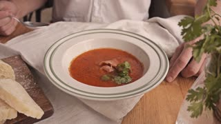 Eating amazing tomato soup with bacon and cilantro