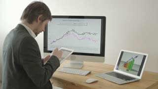 Experienced Businessman Looking at Financial Data with Graphics and charts while