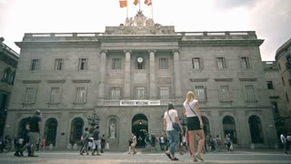 Facade of Barcelona city hall in Sant Jaume square in Catalonia, Spain. Welcome Refugees flag