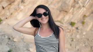 Fashion Portrait of Young Brunette Smiling Woman In Sunglasses With Cliff In Background
