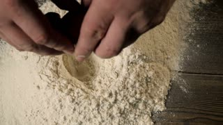 Female Hands Break The Egg Into Flour On Old Wooden Kitchen Table