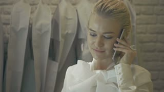 Female sales Assistant in bridalwear store with Smart Phone