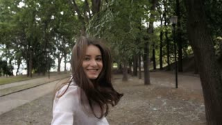 Follow me girl concept. Young pretty happy student model smiling and walking in park
