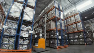 Forklift Truck Driver unloading Pallet In Storage Warehouse