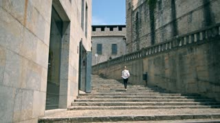 Girl in historical center of Girona go up. Tourist model, a lot of stairs