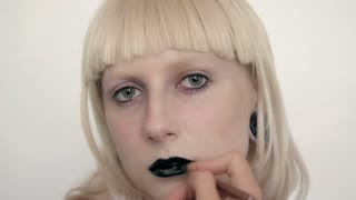 girl in the image of albino with black lips and white eyes. Art beauty face. Picture taken in the studio on a white background