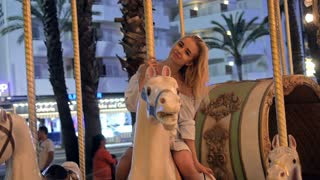 Girl On Old French carousel in a holiday park. Elegant Charming cute girl in fashionable clothes enjoys, sitting on carousel horse