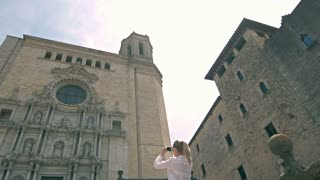 Girl take photo on phone Church of Sant Feliu in Girona Saint Felix , Spain