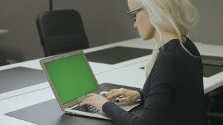 Girl Using Touchscreen on Phone with Green Screen in Office 2