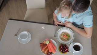 Happy kid girl and woman preparing healthy breakfast together - top view. Mother father and daughter