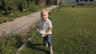 Happy Little Boy Playing With Ball In The Garden. Little Kid Playing Soceer Outdoors