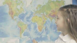 Happy Little Girl Smilesin Front of World Map in Shool