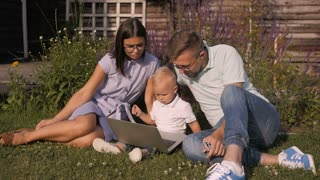Happy Parents With Son Using Laptop While Sitting At Yard