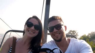 Happy Young Couple On Chair Lift Enjoying Landscape And Making Selfie