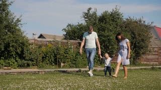 Happy Young Family Having Fun Outdoors. Mom, Dad and Kid Walking, Enjoying Nature Outside