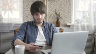 Happy Young Man Freelancer with Modern Laptop Buying by  Credit Card. Online Shopping