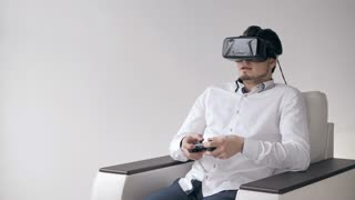Happy Young Man with Virtual Reality Headset or 3d Glasses with Controller Gamepad Playing racing Video Game at home