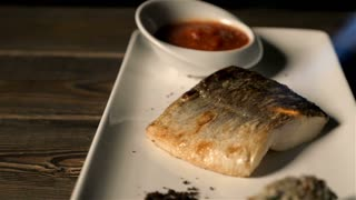 Healthy Food Concept: Chef Fries Fish Served On a Plate With a Gas Burner