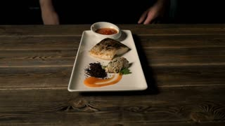 Healthy Food Concept: Chief Serving Hot Baked Fish Piece Over White Plate On Wooden Table