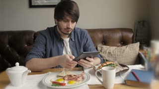 Hipster Man Using Digital Tablet  Eating Healthy Breakfast
