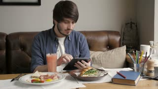 Hipster Man Using Digital Tablet  Eating Healthy Breakfast