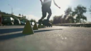 Legs of teenager having roller skate exercise in public park