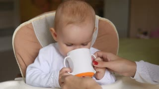 Little girl drink water in Child seat and smiling. Happy family concept. Mother with spoon and baby food
