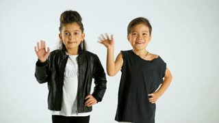 Little Stylish Kids Wave At The Camera And Smile, Isolated On White Studio Shot