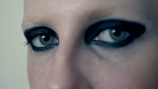 macro portrait of woman eye with black feather, close up eye