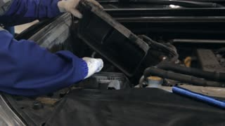 Mechanic checking oil level in a car workshop. Man in truck service checking engine