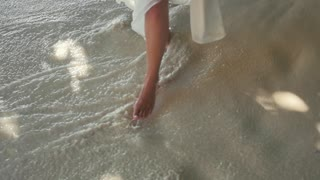 Nice Legs of a Pretty Girl Walking in Water on Beach Exotic Islands