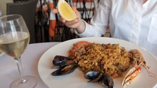 Paella with rice and seafood, delicious food. Lemon squezze by girl in restaurant
