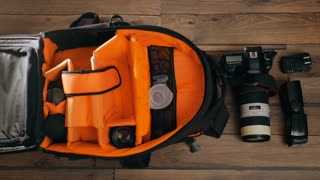 Photographe pack his camera and lenses to bagpack. Bag and appliances for photography top view
