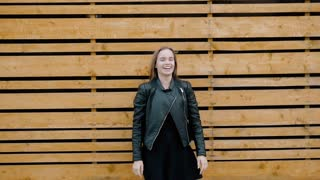 Portrait of a very happy young woman in stylish clothes and leather jacket in park