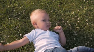 Portrait of a Young Boy Lying In The Grass. Cute Little Boy Having Fun Outdoors On Lawn
