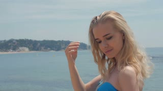 Portrait of attractive woman standing at beach. Happy smiling girl looking at camera at seaside. Young blonde woman relaxing at beach