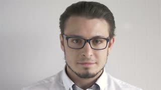 Portrait Of Attractive Young Man With Glasses Standing On Gray Background