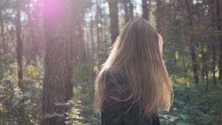 Portrait of beautiful young brunette sexy woman hair blowing in wind in forest