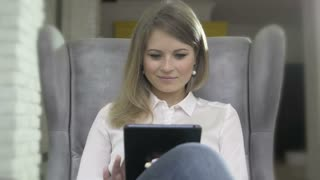 Portrait of Young Beautiful Smiling Woman Using Tablet PC Sitting In Armchair