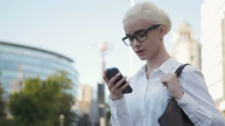 Portrait of Young Business Woman Typing Text Message On Phone Outdoors