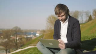 Portrait of Young Man Using Laptop Outdoors Sitting On The Grass In Park
