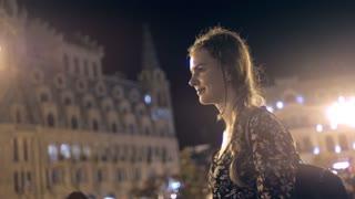 Pretty girl in the night city walking. City lights
