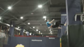 Professional gymnast doing trcks on trampoline. Going on Vertical Wall. Amazing tricks