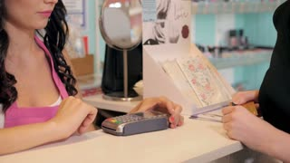 Profile view of a pretty young woman paying with a credit card at a store
