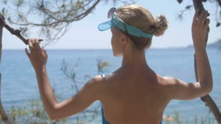 Rear view of relaxed woman on summer travel vacation to the coast sea