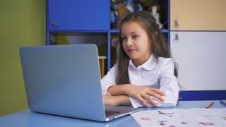 SchoolGirl Studying at the Library Doing after lessons Homework with laptop PC. Elementary school with devices. Child reading