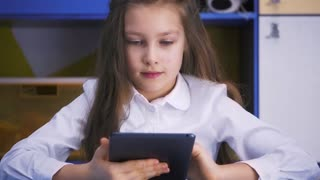SchoolGirl Studying at the Library Doing after lessons Homework with tablet PC. Elementary school. Child reading