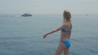 Sexy blonde Woman looking at sea, sky, boat from sea side